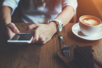 mani che usano smartphone in un bar - cappuccino